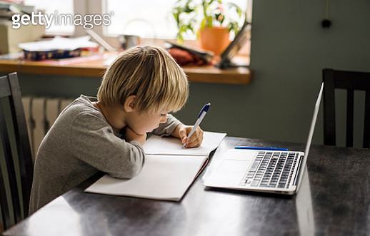 Young boy making notes while using laptop - gettyimageskorea