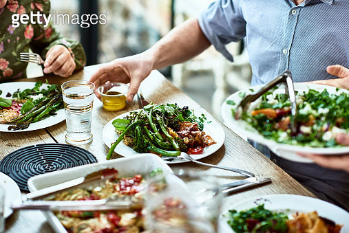 Close up shot of people sitting at dining room table with plates of vegetables and salad, person serving guests at dinner party, man about to pour dressing on his meal - gettyimageskorea