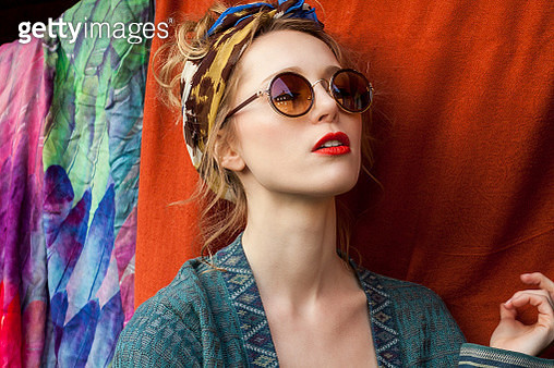 Close-up of thoughtful stylish woman wearing sunglasses against fabric - gettyimageskorea
