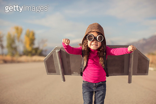 A young girl is wearing goggles and a flight cap and is ready to take to the sky. She has made her own jet pack and is ready to fly away to her dreams. The girl is standing on a road in rural Utah, USA. Girls have big ideas too. - gettyimageskorea