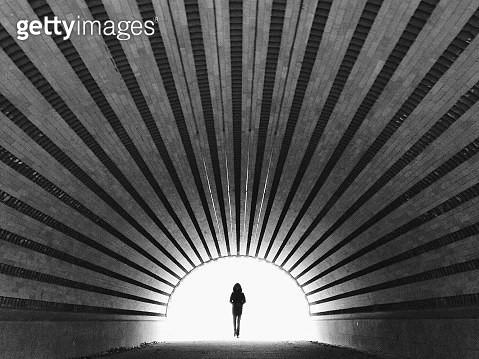 Silhouette Woman Walking In Tunnel - gettyimageskorea