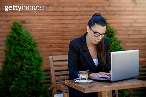 Young businesswoman working on laptop at a café - gettyimageskorea