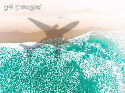 Airplane flying above San Francisco beach with surfers. - gettyimageskorea
