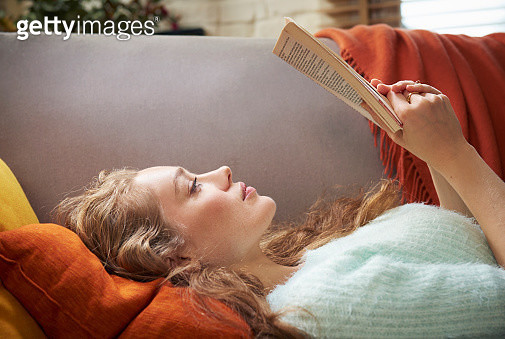 Young woman lying on sofa reading - gettyimageskorea