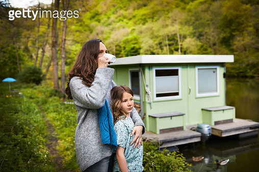 Mother embracing her daughter on the shore near a houseboat - gettyimageskorea