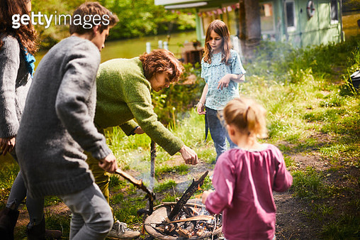 Family preparing a campfire together - gettyimageskorea