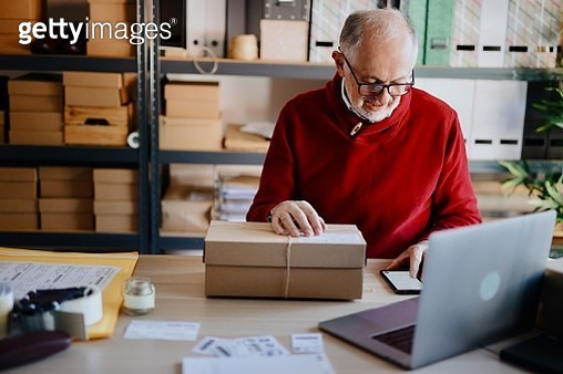 Online business owner looking at laptop while preparing deliveries for clients - gettyimageskorea