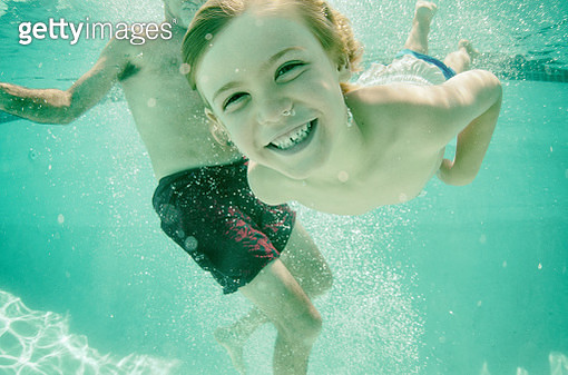 Happy child swimming with his grandpa underwater - gettyimageskorea