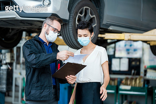A Customer Service explaining fixing detail of car to female client at an auto repair center. Customer Service, Quality of Service. - gettyimageskorea