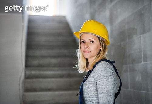 Young Woman Worker With A Yellow Helmet On The Construction Site. - gettyimageskorea