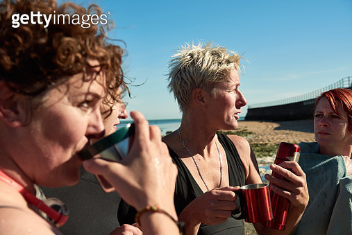 Friends enjoy a hot drink after a swim in the sea - gettyimageskorea