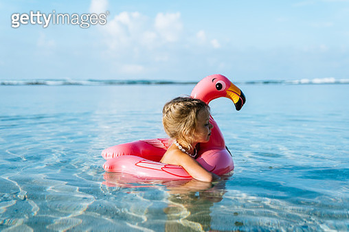 Adorable little blond girl with pink inflatable flamingo swimming in a tropical ocean on summer vacation. - gettyimageskorea