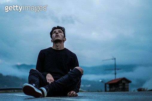 Young Man Sitting Against Sky - gettyimageskorea