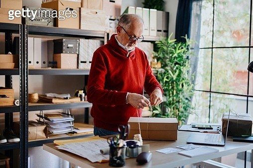 Senior man owner of small business packing product in box preparing it for delivery - gettyimageskorea