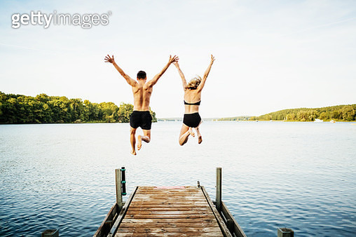 Two friends jumping with their arms in the air off the end of a jetty at a lake together. - gettyimageskorea