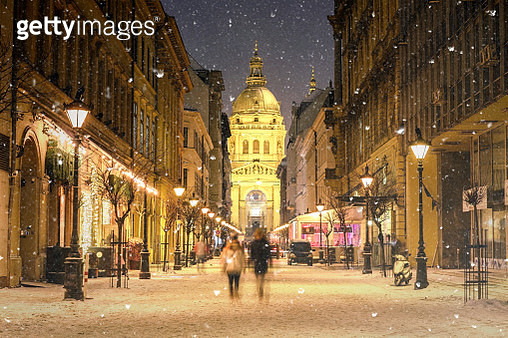 Illuminated cityscape of Zrinyi Street in Budapest with St Stephen's Basilica in a snowy winter landscape at dusk - gettyimageskorea