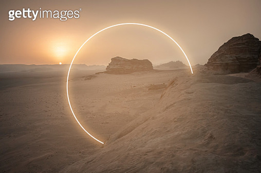 Futuristic circle made with neon lights in the desert landscape. - gettyimageskorea