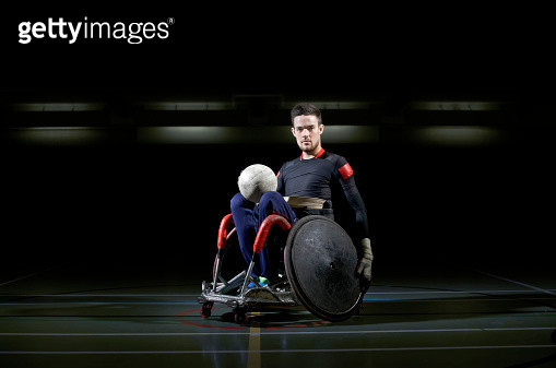 Wheelchair rugby athlete in chair with ball - gettyimageskorea