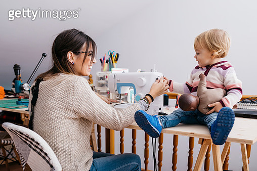 Happy mother with little daughter at home using sewing machine - gettyimageskorea