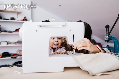 Little daughter watching her mother using sewing machine at home - gettyimageskorea