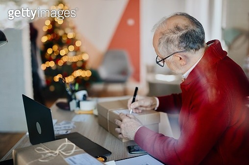 Senior man accepting new orders online and packing merchandise for customer - gettyimageskorea