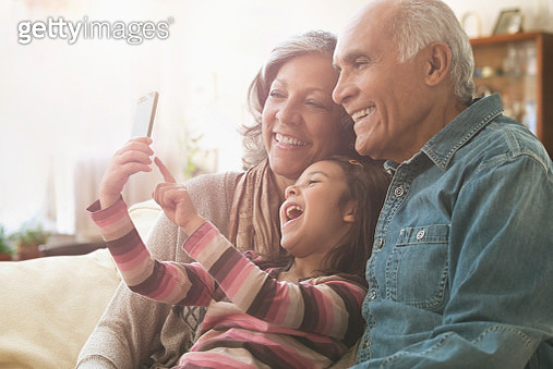 Grandparents and granddaughter taking selfie on sofa - gettyimageskorea