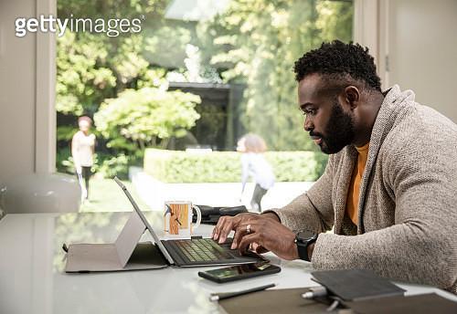 Black man using digital tablet working from home - gettyimageskorea