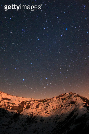Constellations Leo and Virgo above snow-covered mountains lit by the rising moon. - gettyimageskorea