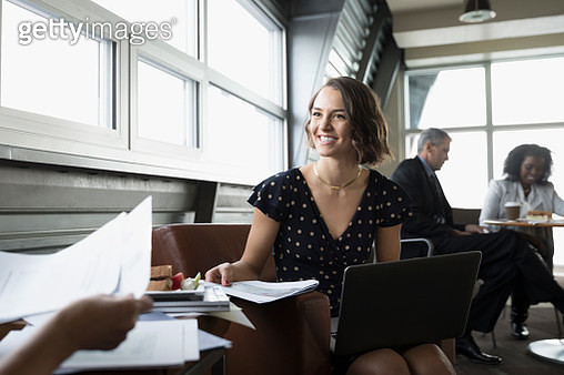 Smiling, confident businesswoman with paperwork using laptop in business lounge - gettyimageskorea