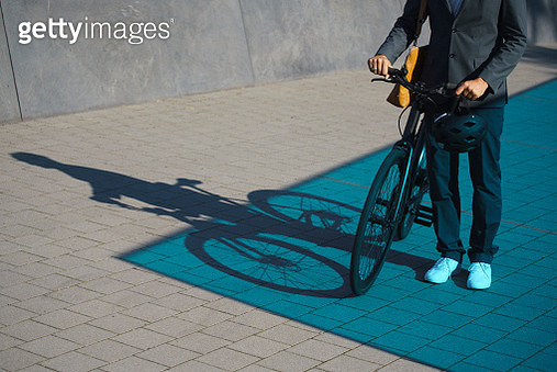 Low section of businessman standing with bicycle on street - gettyimageskorea