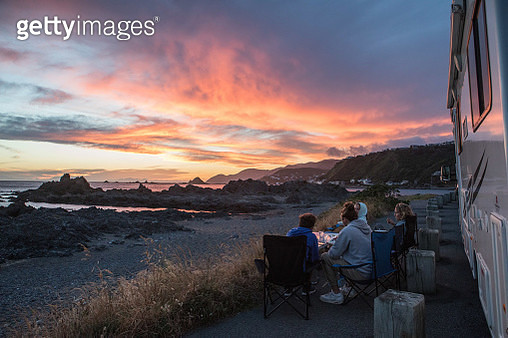 Friends On Road By Camper Van Against Sky During Sunset - gettyimageskorea
