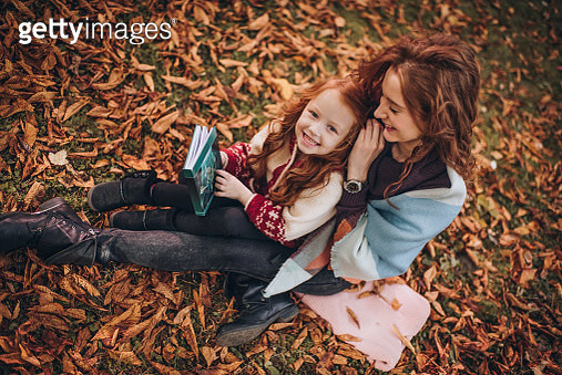Above view of happy mother and daughter with a book in autumn leaves. - gettyimageskorea