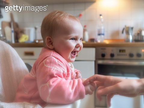 Happy baby girl in sitting in high chair in kitchen - gettyimageskorea