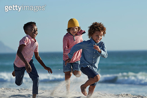 Kids playing together on beach in sunlight - gettyimageskorea