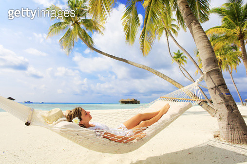 Young woman resting in a hammock against the palms. - gettyimageskorea