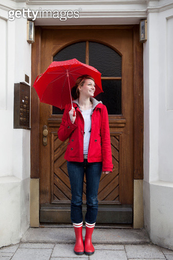 Woman with umbrella in front of house - gettyimageskorea