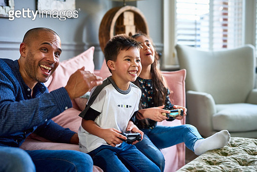 Candid portrait of mature man sitting on sofa with boy and girl, having fun, winning, competition - gettyimageskorea