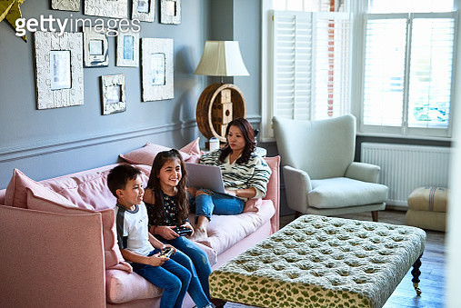 Brother and sister playing video games at home on the weekend, mid adult woman working from home, comfort, relaxation, multi tasking - gettyimageskorea