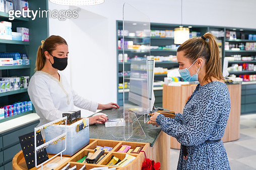Pharmacist charging the client for the medicine - gettyimageskorea