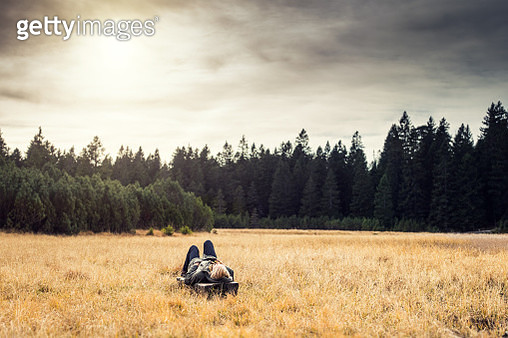 Young woman relaxing in nature. She is lying on the bench surrounded by pine forest. - gettyimageskorea