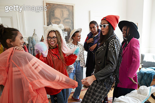 Smiling young multi-ethnic female friends wearing clothes in bedroom while enjoying slumber party at home - gettyimageskorea