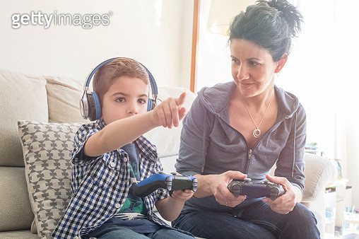 Mother and son playing with Videogames joystick - gettyimageskorea
