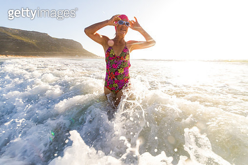 Senior woman going for a morning swim in the sea - gettyimageskorea