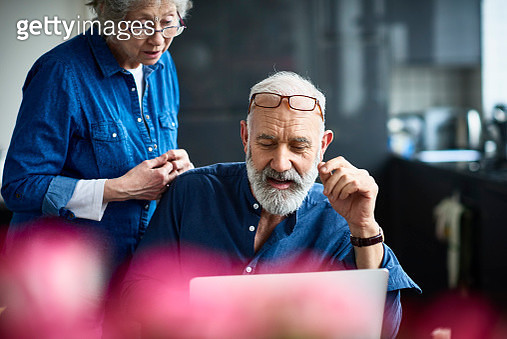 Candid portrait of senior couple at home, man with grey hair and beard working on computer, glasses resting on forehead, seniorpreneur working from home with wife - gettyimageskorea