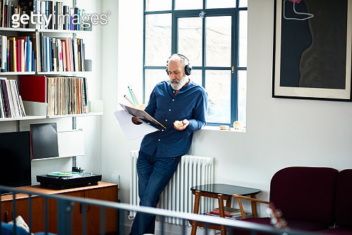 Senior males Hipster wearing headphone, leaning on windowsill, reading album cover, engrossed in music, listening to favourite song, music fan - gettyimageskorea