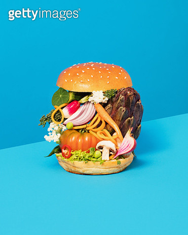 Still life image of a burger with lots of raw vegetables between two buns. - gettyimageskorea