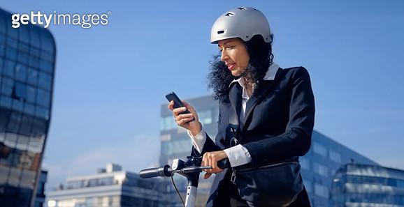 Businesswoman using smart phone in city - gettyimageskorea