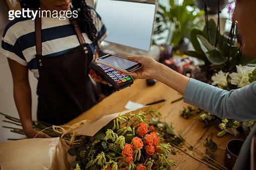 Close up of a young woman paying for a bouquet with her phone - gettyimageskorea