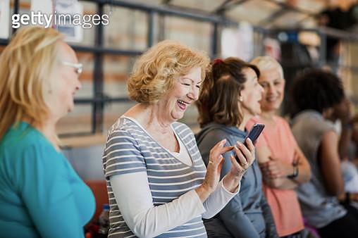 Senior woman using smartphone before dance class - gettyimageskorea