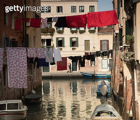 A colorful Venetian canal scene with clotheslines at sunset. - gettyimageskorea